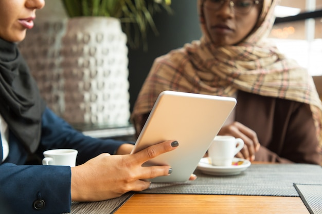 Женский коллеги смотрят контент на планшете