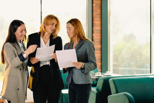 現代のオフィスにいる女性の同僚、若いビジネスウーマンが新しいビジネスプランについて話し合っています。チームワークの概念。