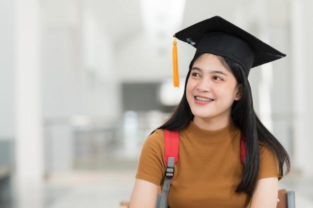黒い帽子と黄色いタッセルを身に着けて、卒業式の日に笑顔で幸せな女子大生