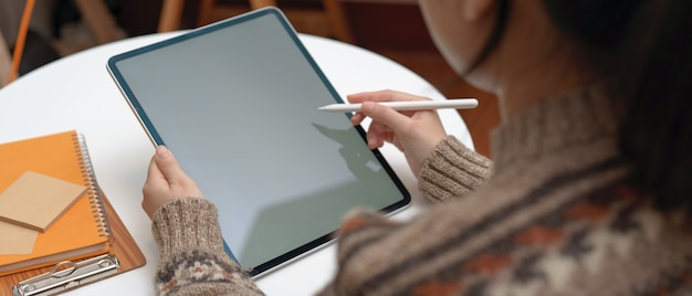 Female college student doing assignment with vertical mock-up tablet and stationery on coffee table