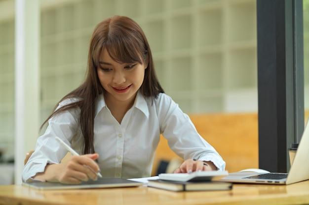 Студентка колледжа делает домашнее задание и читает лекцию на планшете в библиотеке