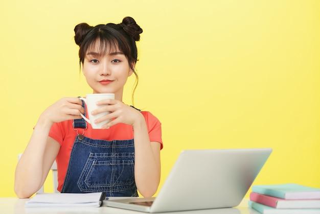 オンラインクラスを開く前に一杯のコーヒーを飲む女子大生