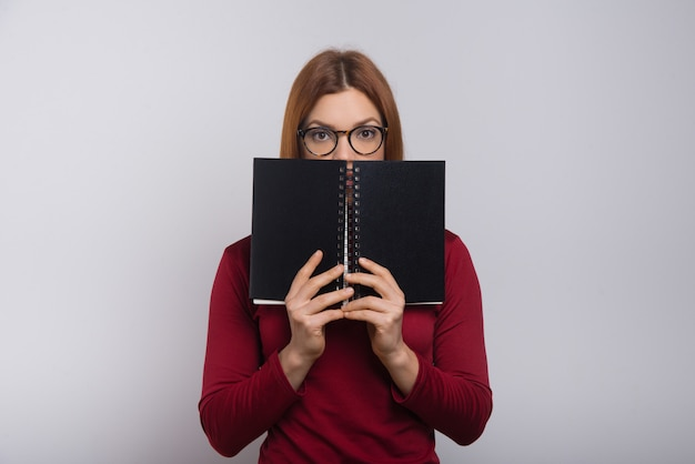 Female college student hiding behind notebook