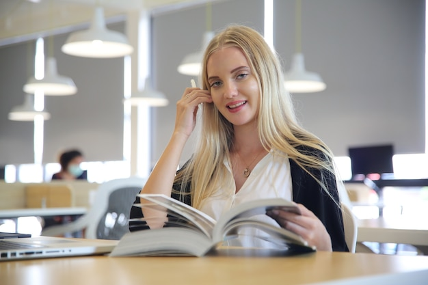 Female college student reading a book in library