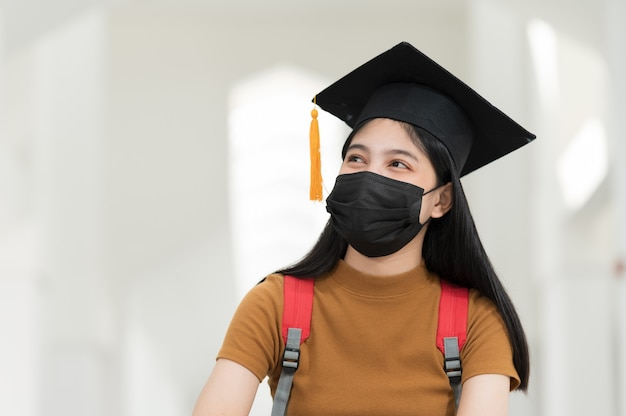 Female college students, university graduates, wear black hats, yellow tassels and wear masks during the epidemic.