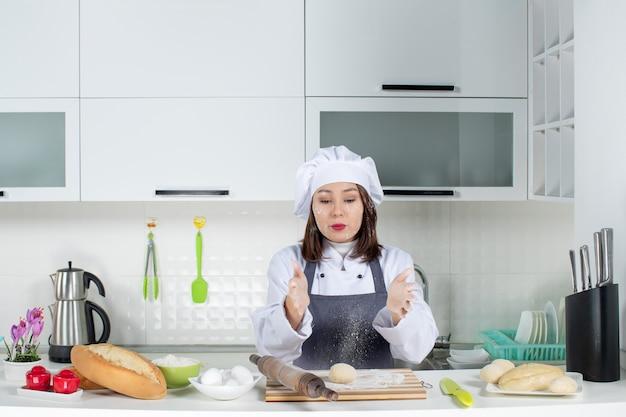 白いキッチンで小麦粉で顔を汚すテーブルの後ろに立っている制服を着た女性コミシェフ