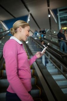 에스컬레이터에서 휴대 전화를 사용하는 여성 통근