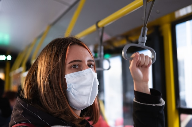 Female commuter wears a protective mask in public transport. coronavirus, covid-19 spread prevention concept, responsible social behaviour of a citizen