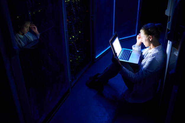Female computer scientist working at night