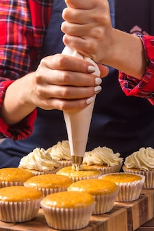 Female confectioner in a blue apron and a plaid red shirt applies cream to cupcakes