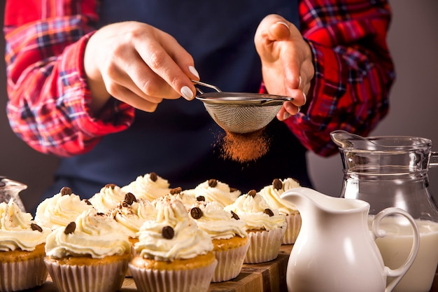 Female confectioner decorates cupcakes with tiramisu cocoa powder
