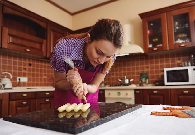 手作りのチョコレートトリュフを準備するために、菓子バッグから収穫されたキャンディー型に甘いクリーミーな液体を絞り出す女性の菓子職人