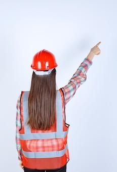 Женский инженер-строитель в красном шлеме и защитной маске, указывая вперед.