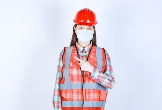 赤いヘルメットと左向きの防塵マスクの女性建設エンジニア。