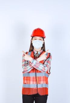 赤いヘルメットと安全マスクを身に着けた女性の建設エンジニアが上に何かを示しています。