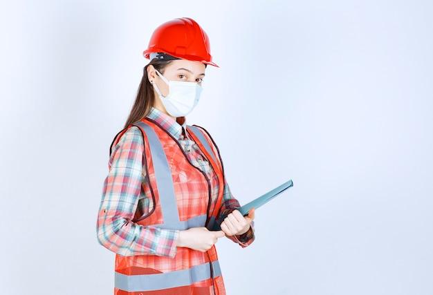 青いフォルダーを保持している安全マスクと赤いヘルメットの女性建設エンジニア。