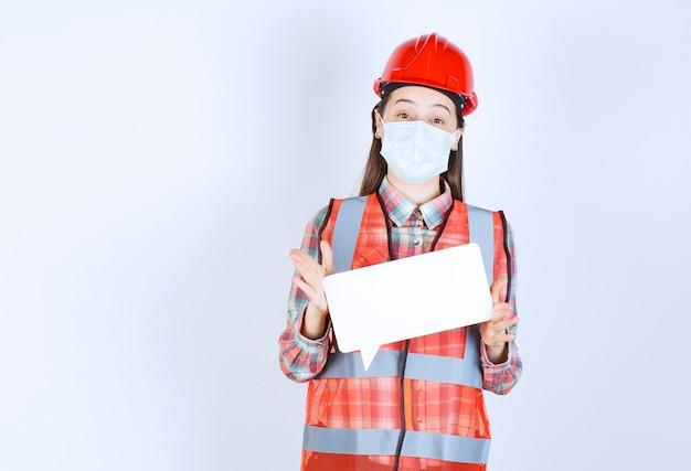 安全マスクと長方形の空白の情報ボードを保持している赤いヘルメットの女性の建設エンジニア。