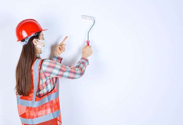 안전 마스크와 빨간 헬멧 트림 롤러를 들고 파란색으로 벽을 그리는 여성 건설 엔지니어.