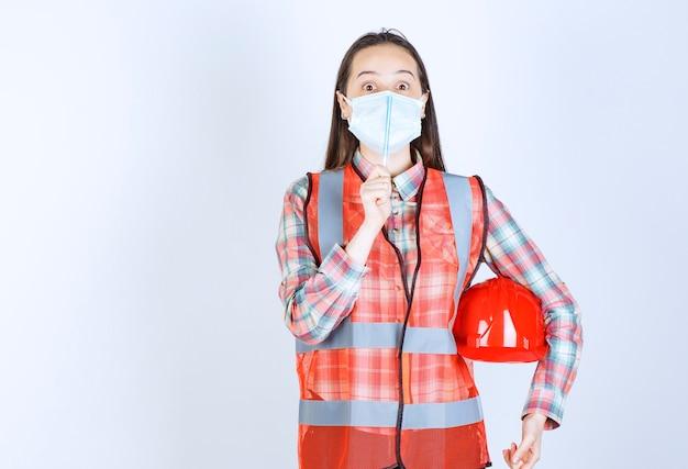 Ingegnere edile femminile in maschera di sicurezza e un casco rosso sotto le braccia che tiene una penna e sembra confuso e pensieroso