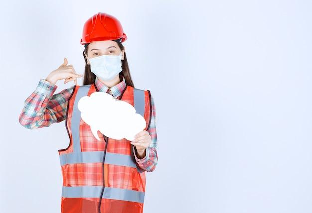 Ingegnere edile donna con maschera di sicurezza e casco rosso che tiene una scheda informativa a forma di nuvola e chiede una chiamata