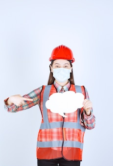 Female construction engineer in safety mask and red helmet holding a cloud shape info board.