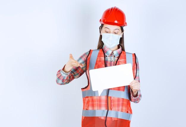 Ingegnere edile donna con maschera di sicurezza e casco rosso con in mano una scheda informativa vuota rettangolare