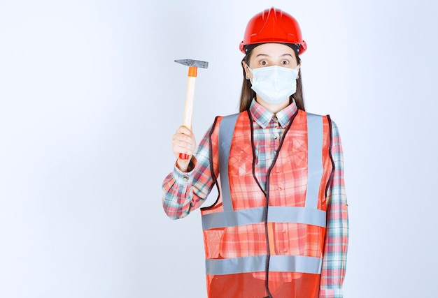 Female construction engineer in safety mask and red helmet holding a wooden handled ax, looks confused and does not know what to do