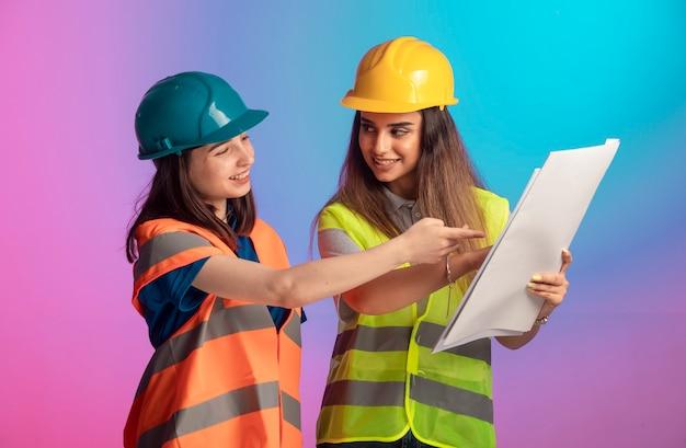 함께 일하고 화려한 배경에 프로젝트 계획을 논의하는 여성 건설 엔지니어.