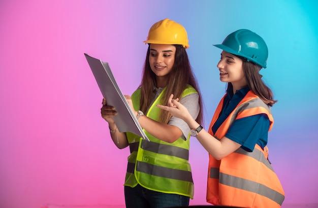 女性の建設エンジニアが協力して、カラフルなプロジェクト計画について話し合っています。