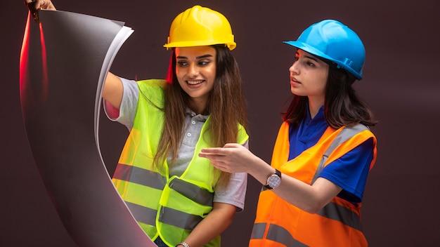 女性の建設エンジニアが協力してプロジェクト計画について話し合っています。