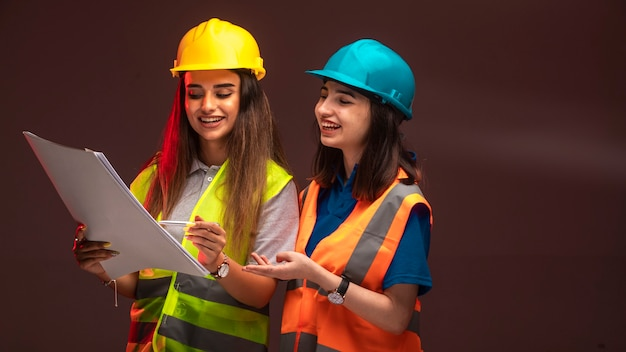 Женщины-инженеры-строители работают вместе и обсуждают план проекта.