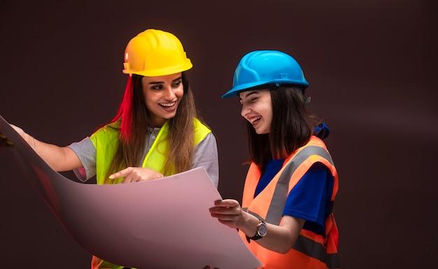 Ingegneri edili femminili che lavorano insieme e discutono il piano di progetto.