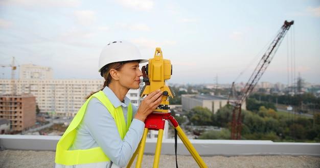 女性の建設マネージャーとエンジニアは、建築現場で作業するエンジニア機器を備えた保護ヘルメットを着用しています。
