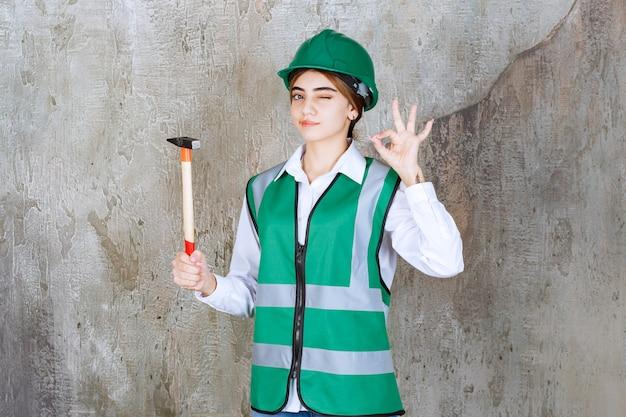 ハンマーを保持し、okサインを与える緑のヘルメットの女性建設労働者