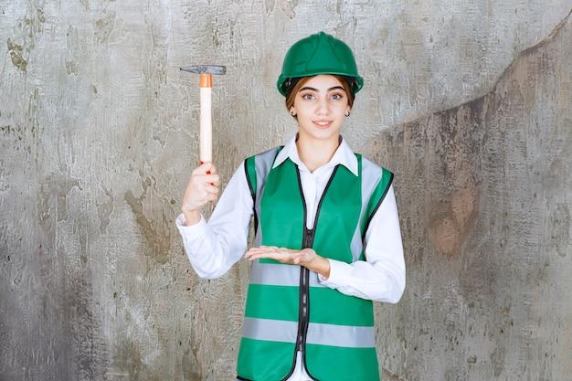ハンマーでポーズをとって緑のヘルメットの女性建設労働者