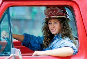 ハード帽子の運転トラックの女性の建設労働者