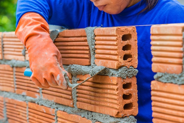 Female construction worker laying down brick wall