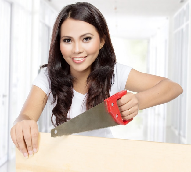Female construction worker with saw