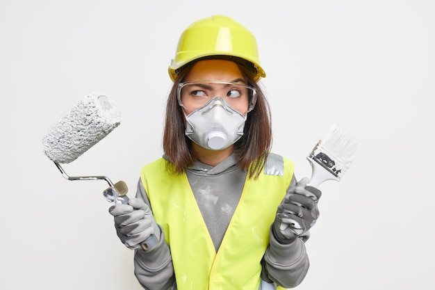 Ingegnere edile femminile in giubbotto di sicurezza occhiali protettivi maschera e guanti elmetto tiene l'attrezzatura sembra seriamente da parte pronta per entrare nell'area dell'edificio per l'ispezione. operaio industriale.