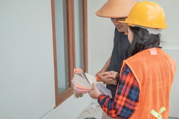 Female constructor and mason discussing paint examples in the background of building construction