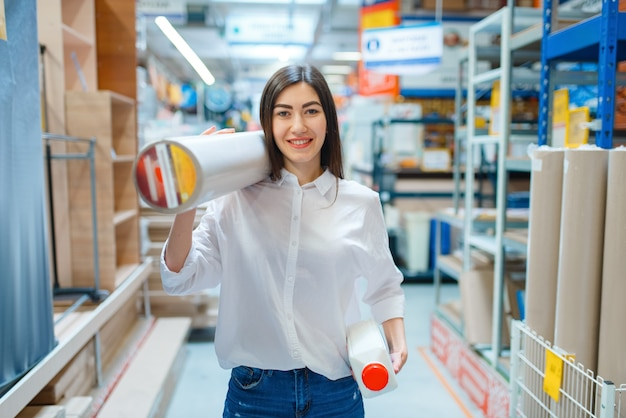 Female consumer buying wallpapers in hardware store.