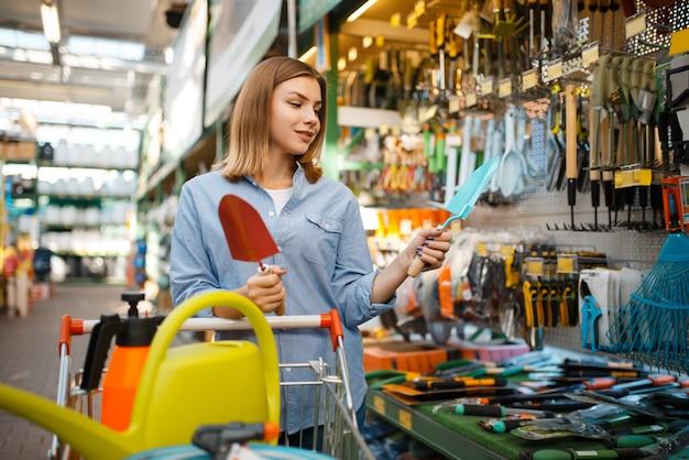 庭師のための店で庭のシャベルを選ぶ女性の消費者。花卉園芸用の店で機器を購入する女性、花卉楽器の購入