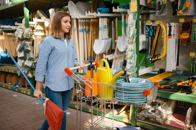 庭師のための店でガーデニングツールを選択する女性の消費者。花卉園芸用の店で機器を購入する女性、花卉楽器の購入