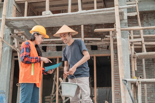 Female contractor and builder discuss building designs in the background of building construction