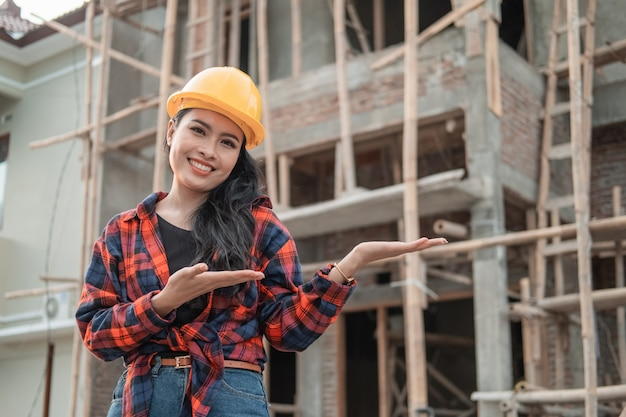 Female contractor wearing a safety helmet in the background of building construction