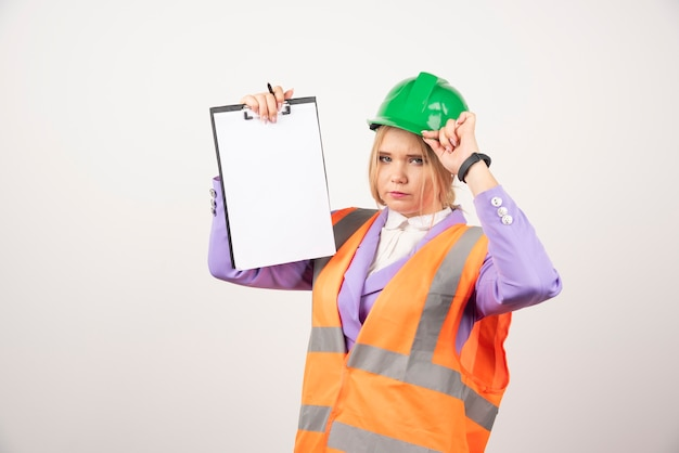 Female contractor with green helmet holding clipboard on white wall.