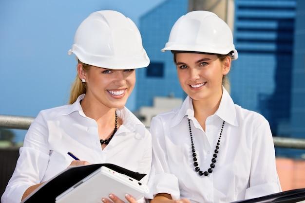 Женщины-подрядчики перед строительной площадкой (акцент на блондинке)