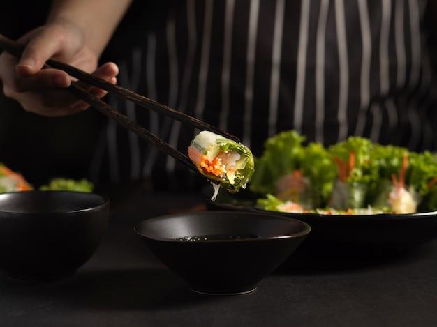 Женщина-повар сжимает вьетнамские блинчики с начинкой палочкой для еды