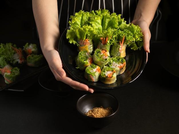 Руки повара держат тарелку вьетнамских рулетов с начинкой с соусом на столе