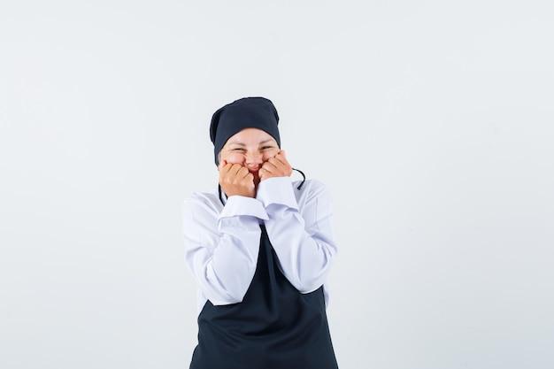 制服、エプロン、喜びに見える、正面図で頬に拳を保持している女性料理人。